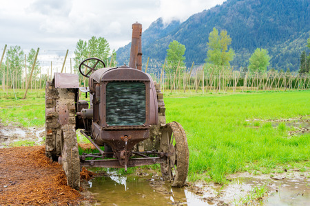Antiquated rusty tractor on a real farm with historical engineering design of farm equipment from days old.
