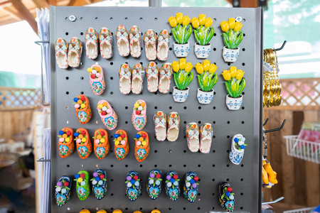 Dutch magnet souvenirs of porcelain garden clogs and tulips, with fancy designs in different colours, in a tourist gift shop, selling momentos from Holland.