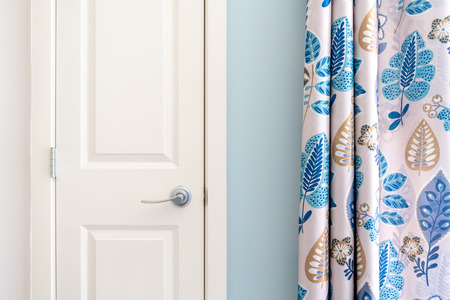 Home interior showing  colonial closet door with blue curtain decor and light blue painted wall. Stock Photo
