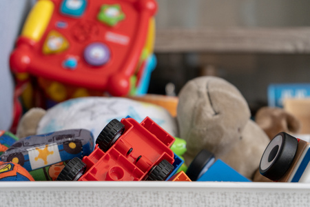 Close up of a box of toys, with many different objects including soft toys, play cars and toddler toys.
