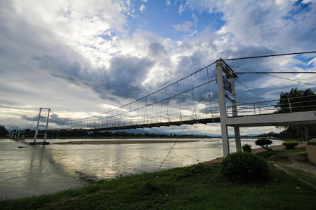 The old wooden bridge Bridge (Rattanakosin suspension bridge) across the Ping river (hanging bridge) at Tak Province, thailand