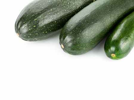 Three courgettes on white background with copy space photo