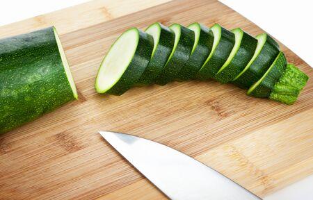 cucurbit: Sliced zucchini on a wooden cutting board