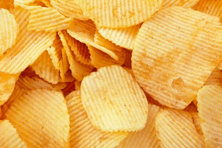 Golden potato chips background, closeup studio shot