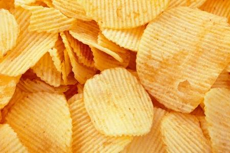 Goldene Kartoffel-Chips Hintergrund, Nahaufnahme Studio erschossen Standard-Bild