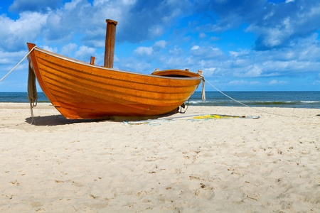 shore line: Wooden fishing boat on a sandy beach in sunny day