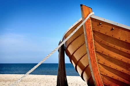 Front view of a wooden fishing boat, sea in background and blue sky with copyspace