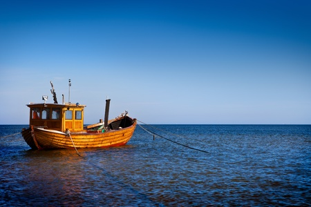 small boat: Fishing boat floating on the water, blue sea and sky with copyspace Stock Photo