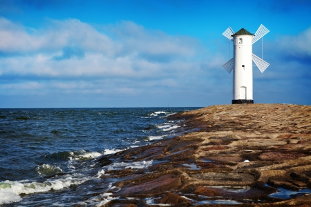 White old lighthouse in Swinoujscie, stone pier and wavy sea, Poland