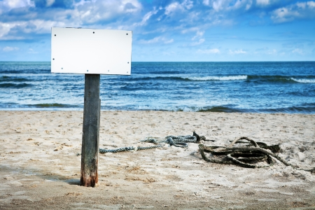 Blank white board on wooden pole on sandy beach, cloudy sky and sea in background Stock Photo - 13753895