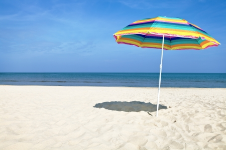 beach umbrella: Colorful beach umbrella on the sandy beach on summer day  Blue sky and sea in the background