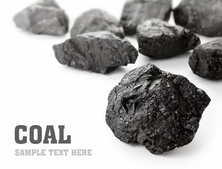 Carbón agrupa derramado sobre fondo blanco, con copia espacio