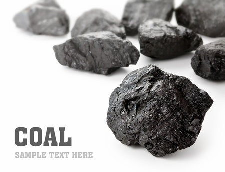 Coal lumps spilled on white background with copy space photo
