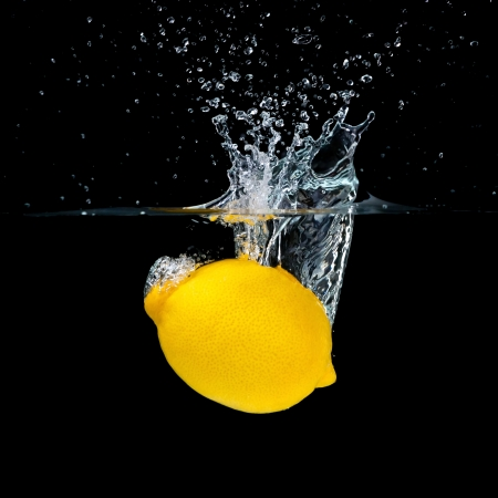 Fresh lemon falling into water. Isolated on black background