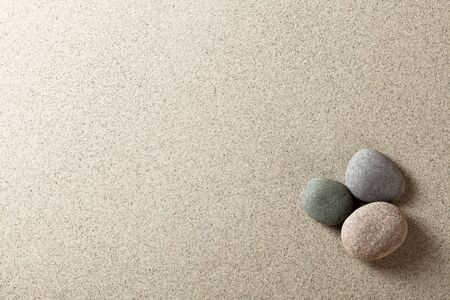 peaceful background: Three colorful round stones on sand background