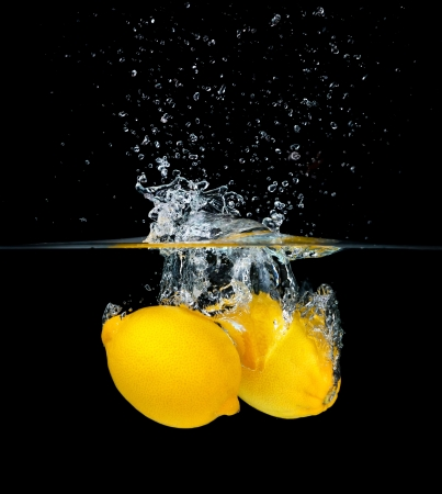 Two fresh lemons falling into water, isolated on black background photo