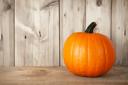 Pumpkin on wooden table against wooden background
