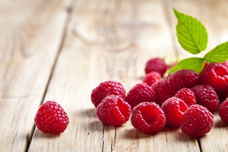 raspberries: Raspberries with leaf on wooden table background. Copy space Stock Photo