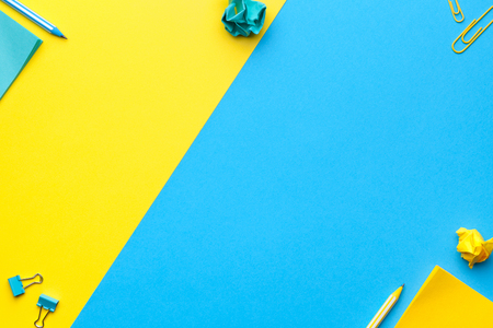 School, office accessories on blue, yellow background. Copy space. Top view