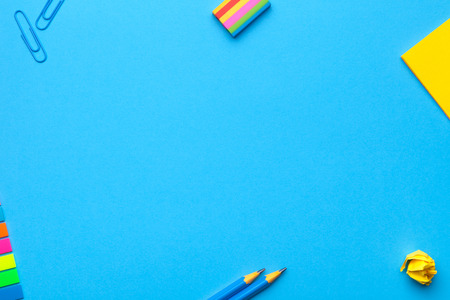 School accessories on blue background. Minimal style. Flat lay. Copy space. Top view