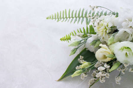 Flower arrangement of several kinds of white flowers and leaves.