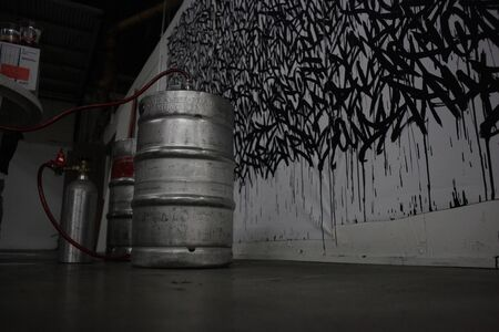 A keg of beer sits in front of wall art