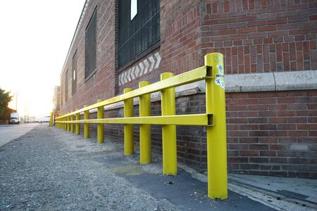 perspectiva lineal: A yellow fence in front of a brick wall Foto de archivo
