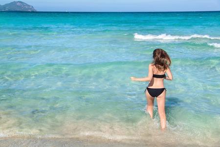 Young woman running into the water, Playa de Muro, Mallorca, Spain.