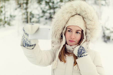 Girl taking selfie. Christmas girl outdoor self portrait. Woman in winter clothes on a snow field. Toned picture Archivio Fotografico