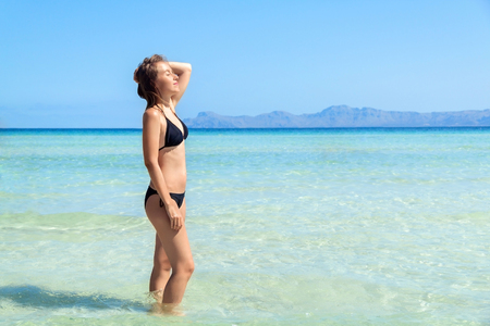 Young woman in bikini standing with her hand over head enjoying hot summer day on the beautiful beach of Alcudia, Mallorca, Spain. Stock Photo - 83717584