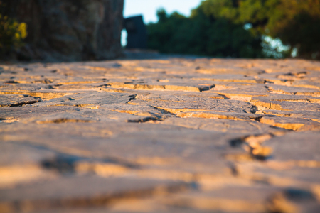 Close up view on the road pavement bricks. Old cobblestone walkway.