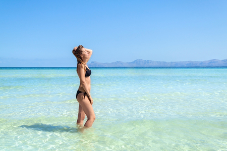 Young woman in bikini standing with her hand over head enjoying hot summer day on the beautiful beach of Alcudia, Mallorca, Spain.