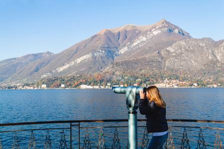 Young girl looking through a coin operated binoculars. Bellagio, Como Lake, Italy. Archivio Fotografico