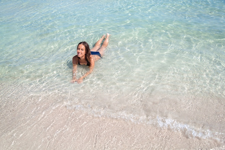 Young woman lying in clear sea water of the beautiful Alcudia beach in Mallorca, Spain. Stock Photo