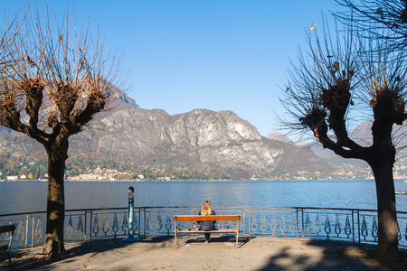 Young girl sitting on a bench looking at lake and mountains. Como Lake, Italy.