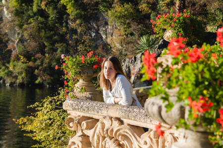 Young girl standing on the old terrace  balcony with flowers. Villa Balbianello. Lake Como, Italy Archivio Fotografico