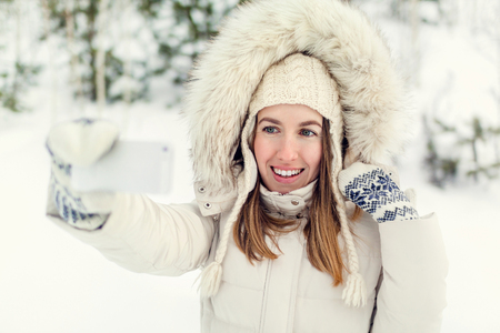 Girl taking selfie. Christmas girl outdoor self portrait. Woman in winter clothes on a snow field.