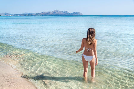 Young woman getting into the water, Can Picafort, Mallorca, Spain.