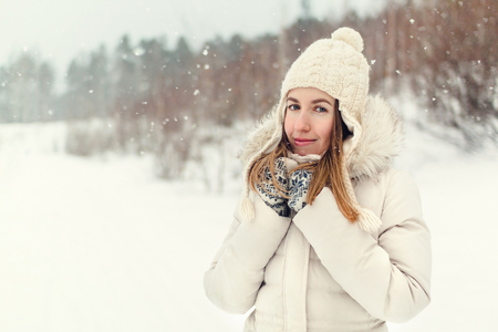 Christmas girl outdoor portrait. Woman in winter clothes on a snow field. Toned picture
