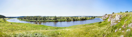 Panoramic view at the rocky shore with a village in the distance. Russian nature. Stock Photo