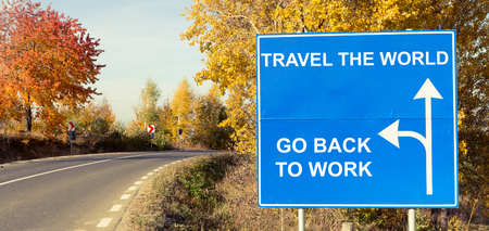 Travel the world or go back to work concept on road sign outdoors on a sunny autumn day Stock Photo