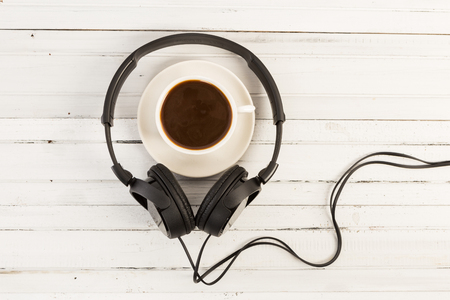 Coffee break and music concept with headphones and cup on white wooden table
