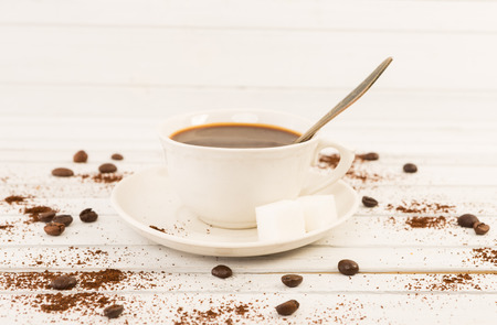 old desk: Ceramic coffee cup with two cubes of sugar on white wooden background and beans Stock Photo