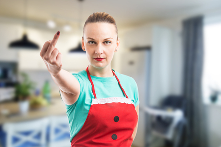 Wife or maid showing middle finger on indoor background wearing red cleaning apron