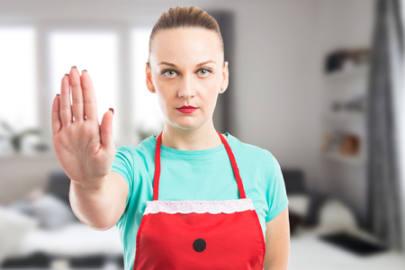 Private maid or housekeeper showing stop stay gesture using hand palm on inside home background Stock Photo