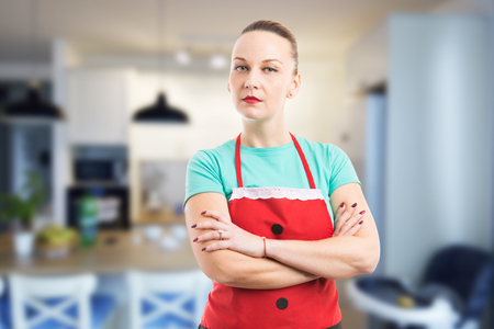 Proud maid, housewife or housekeeper standing arms crossed on clean room kitchen background Stock Photo