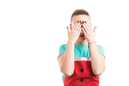 Ama de casa doméstica cubriendo sus ojos y vistiendo un delantal rojo después de cocinar aislado sobre fondo blanco