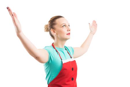 Mujer que lleva el delantal rojo que levanta levantando ambas manos y que parece para arriba aislado en el fondo blanco