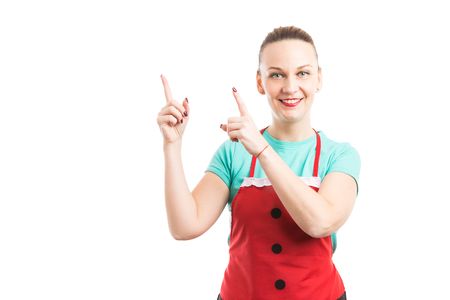 Supermarket or hipermarket employee showing and pointing up to copy space and text area wearing red apron and smiling friendly trustworthy happy Stock Photo