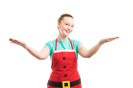 Woman with red apron making invitation and presentation gesture as Christmas supermarket or hipermarket employee Stock Photo